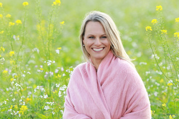 Happy mature woman in flowerfield