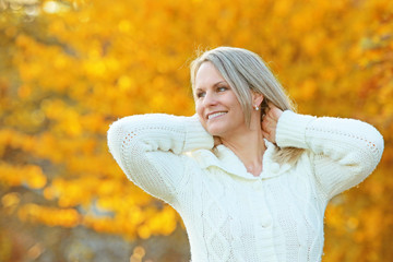 Happy mature woman in front of golden autumn leaves