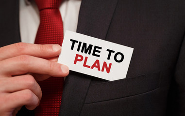 Businessman putting a card with text TIME TO PLAN in the pocket