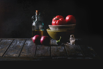 Bowl of tomatoes with purple onion, pepper and bottle of olive oil on old wooden kitchen table. Dark rustic still life.