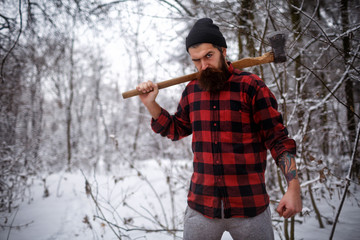 A stylish woodcutter with a long beard cuts a tree in the snow in the woods