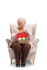 Elderly woman sitting in an armchair and knitting