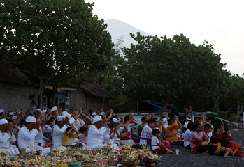 Balinese men and women pray for safety on the beach with Mount Agung in the background, in Amed, on the resort island of Bali