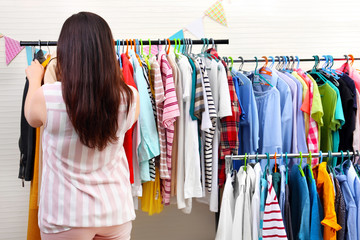 Beautiful overweight woman near rack with clothes at store