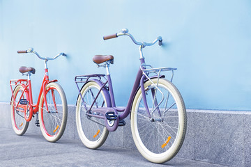 Stylish new bicycles near color wall outdoors