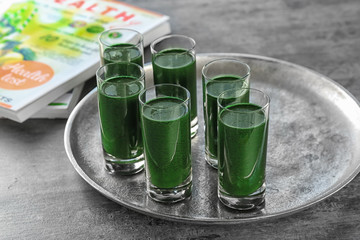 Glasses of fresh green smoothie on metal tray