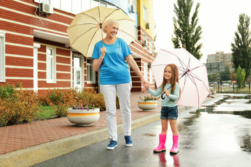 Elderly woman and little girl walking with umbrellas on street