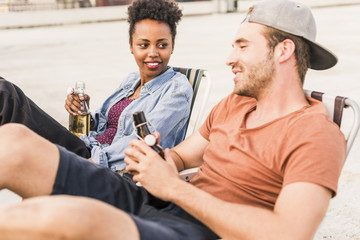Young couple with beer bottles socializing on rooftop