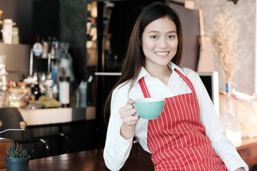 Young asian women Barista holding coffee cup with smiling face at cafe counter background, small business owner, food and drink industry concept