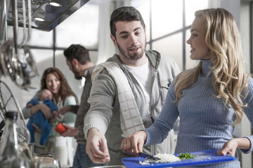 Couple cooking for family and friends in kitchen