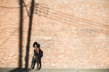 Woman with backpack i front of brick wall with shadow of a power pole