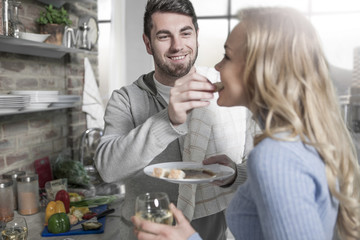 Couple tasting food together in kitchen