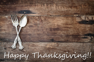 Antique Silverware and Happy Thanksgiving text over Wooden Background