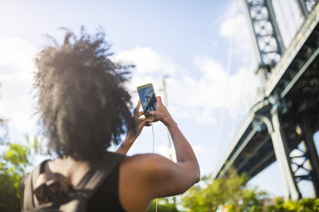 USA, New York City, Brooklyn, woman taking cell phone picture of Manhattan Bridge