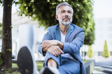 Relaxed businessman sitting outdoors on a wall