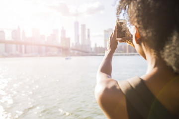 USA, New York City, Brooklyn, woman taking cell phone picture of skyline