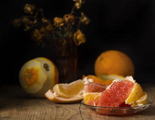 апельсин и грейпфрут лежат на столе натюрморт