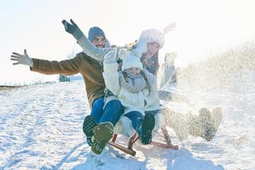 Familie fährt begeistert auf dem Schlitten