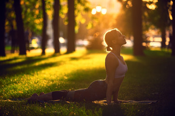 Beautiful young woman practices yoga asana upward facing dog in the park at sunset