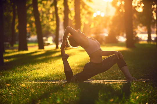 Beautiful young woman practices yoga asana King Pigeon pose rajakapotasana in the park at sunset