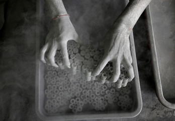 A worker removes paper rolls after filling them with gunpowder mixture to make firecrackers at a factory on the outskirts of Ahmedabad