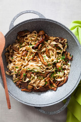 tagliatelle with mushrooms porcini in wok pan on light stone background