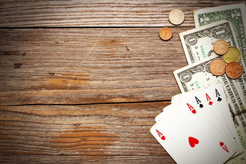 playing cards and cash on rustic wood background