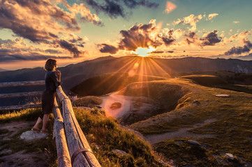 Girl watching a beautiful sunset in a peaceful and tranquil place, Mount Pizzoc summit, Veneto, Italy
