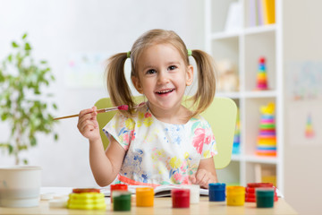Cute child girl painting picture on home interior background