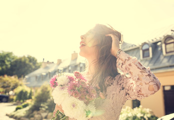 Pretty brunette model with a bouquet of flowers in rays of sun. Vintage toning effect