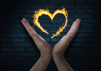 hands with heart fire icon over. Dark bricks wall background