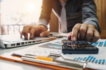 businessman hand working with finances about cost and calculator and laptop with tablet on withe desk at office in morning light