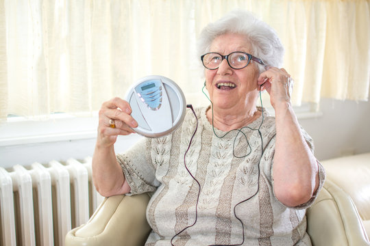 Cheerful senior woman listening to music on CD player at home.