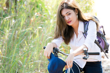 A young woman / traveller in white shirt with smile riding bicycle in national park with green trees