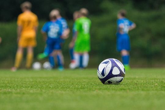 Fußball auf grünem Rasen mit Jugendmannschaft im Hintergrund
