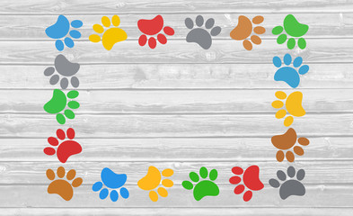 Colorful paw prints animal frame on wooden background with copy space for text.