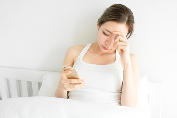 Asian beauty woman have a headache in white bedroom after wake up