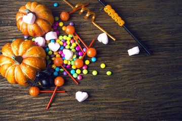 colorful of halloween candy with dessert on wood ground in party concept