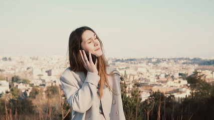 Portrait of young beautiful woman standing on the panoramic view of Rome, Italy. Female talking on the smartphone.