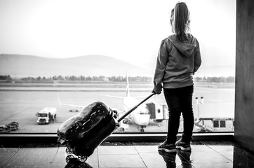 A black-and-white photo of a little girl standing with a suitcase at the airport and looking at her plane.