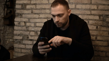 Young handsome man sitting in the cafe with brick wall and using the smartphone, browsing the Internet alone.