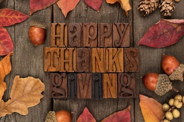 Happy Thanksgiving spelled with wooden letterpress with frame of autumn leaves over a rustic wood background