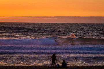 sunset surfer being filmed by a film crew