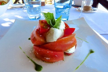 caprese salad with tomatoes, mozzarella cheese and fresh basil stacked on plate