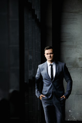 Portrait of stylish male dressed in a suit over grey background