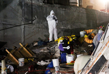 A man puts on a hazmat suit as rescue teams are recovering dead bodies from the rubble of a collapsed building, after an earthquake in Mexico City