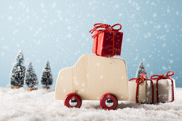 Wooden toy car in winter landscape with gift boxes,  Merry Christmas concept.