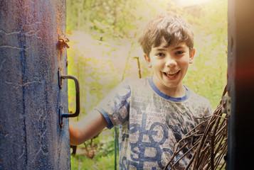 happy teenager boy open shabby door close up smiling photo