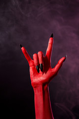 Red devil hand with black sharp nails