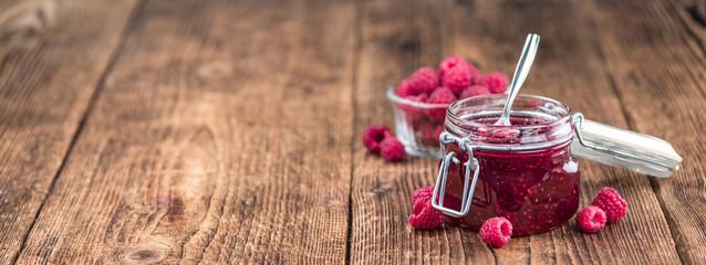 Raspberry Jam on wooden background; selective focus
